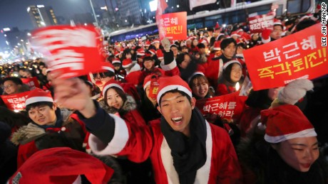 """People wearing Santa Claus costumes shout slogans during a rally calling for South Korean President Park Geun-hye to step down in Seoul, South Korea, Saturday, Dec. 24, 2016. A South Korean special prosecutor on Saturday summoned the jailed friend of impeached President Park Geun-hye who allegedly exploited her connections with Park to extort money and favors from the country's largest companies and manipulate government affairs.The letters read """"Step down, Park Geun-hye."""" (AP Photo/Lee Jin-man)"""