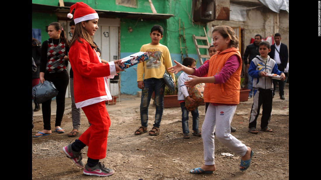 "Chloe, a Lebanese Christian teenager dressed as Santa Claus, hands a gift to a Syrian refugee on December 24, during a gift distribution organized by the Maronite congregation ""Mission de Vie"" in a slum in the town of Dbayeh, north of Beirut."