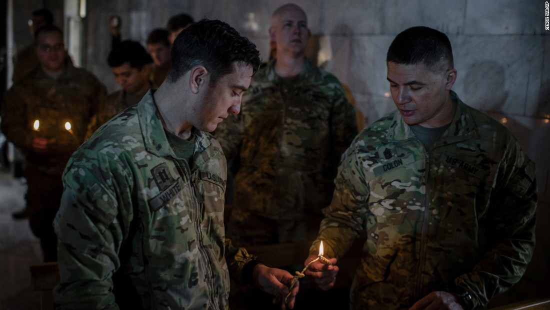 U.S. Army personnel light candles during Christmas Eve Mass in the Assyrian Orthodox church of Mart Shmoni, in Bartella, Iraq.