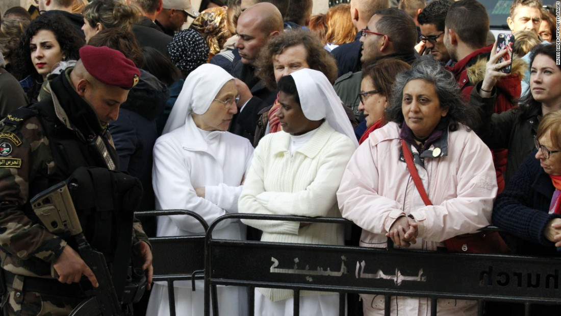 Two nuns are among the spectators taking part in the Christmas Eve celebrations on December 24, outside the Church of the Nativity, revered as the site of Jesus Christ's birth, in the biblical West Bank town of Bethlehem.