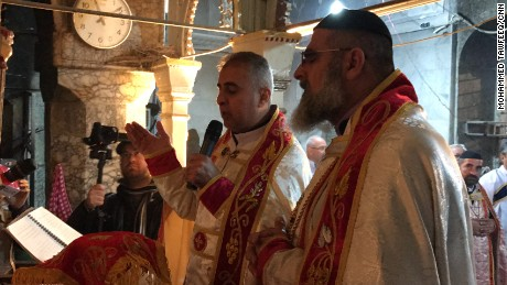 Father Behnam Lalo and another clergyman pray during Christmas mass held at Mart Shmoni in Bartella, Iraq.