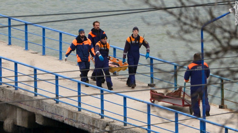 "Russian emergency workers carry remains from the wreckage of the Tu-154 that crashed near Sochi, Russia, on Sunday. The plane was carrying more than 60 members of the Russian army's popular Alexandrov Ensemble, dubbed ""Russia's singing weapon."""