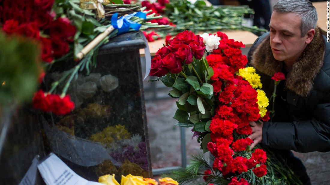 "A man places flowers outside the building of the Alexandrov Ensemble in Moscow on Sunday. Alexander Kibovsky, head of Moscow's culture department, called them ""our cultural paratroopers."""
