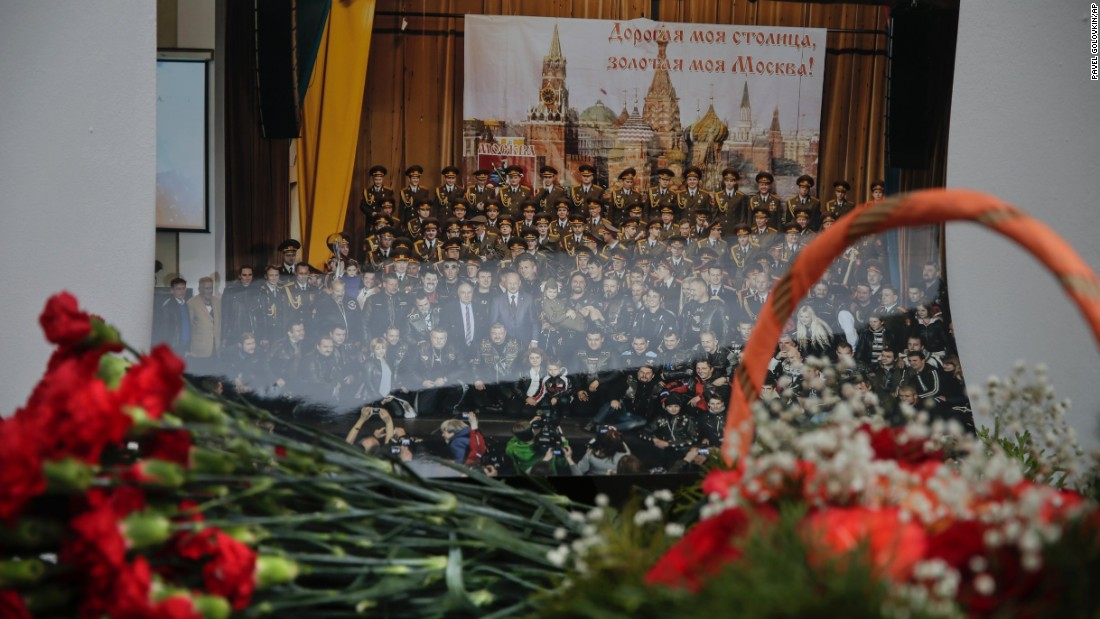 "Flowers lay in front of a photo of the Alexandrov Ensemble at the group's building in Moscow. ""These people always performed in war zones, they wore uniforms, they brought kindness and light,"" Kibovsky said."