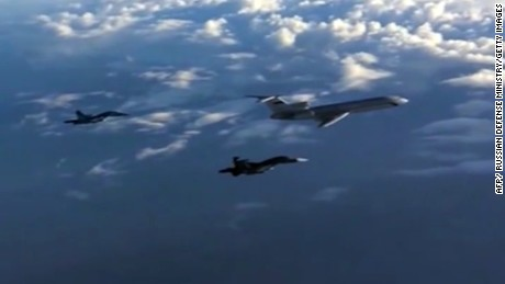 Footage made available on the Russian Defense Ministry's official website on March 15, 2016 reportedly shows Russian SU-34 bombers and a Tupolev Tu-154 transport plane (R) flying above an unknown location en route from Syria. (File photo)
