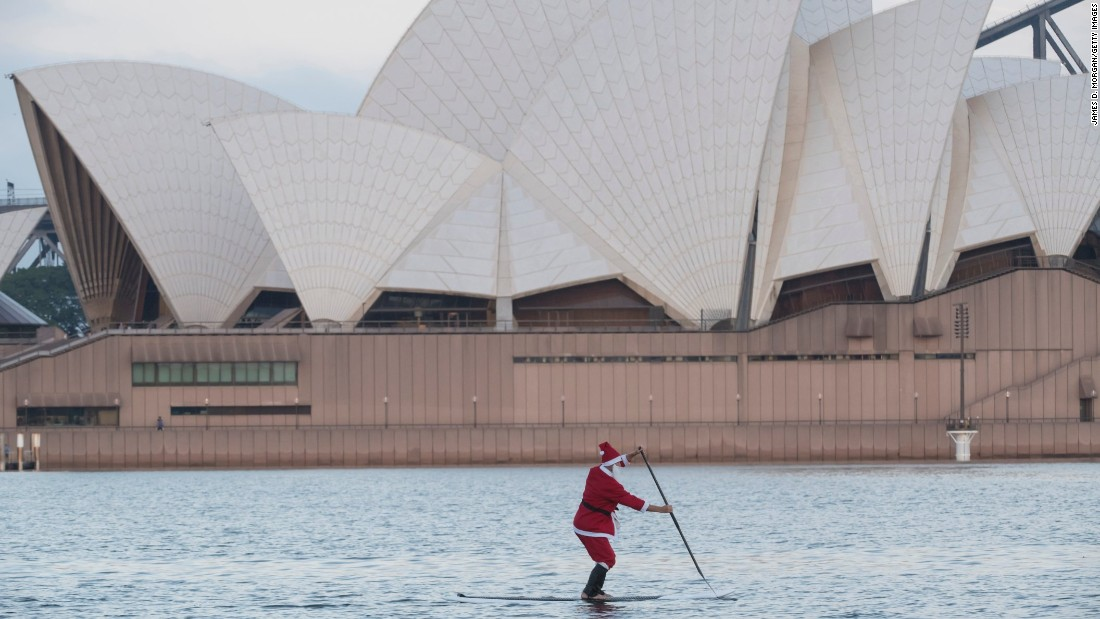 A man wearing a Santa outfit paddleboards in Sydney Harbour on Christmas Day in Australia.