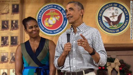 US President Barack Obama addresses troops with First Lady Michelle Obama at Marine Corps Base Hawaii in Kailua on December 25, 2016.