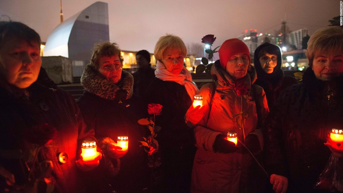 People hold a candlelight vigil for victims of the crash on Sunday, December 25, in Sochi.