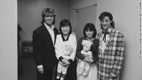 George Michael and Andrew Ridgeley of Wham! pose with fans.