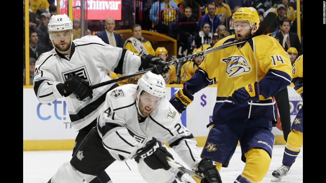 Nashville's Mattias Ekholm, right, takes a stick to the face from Los Angeles' Marian Gaborik during an NHL game in Nashville on Thursday. Los Angeles won 4-0.