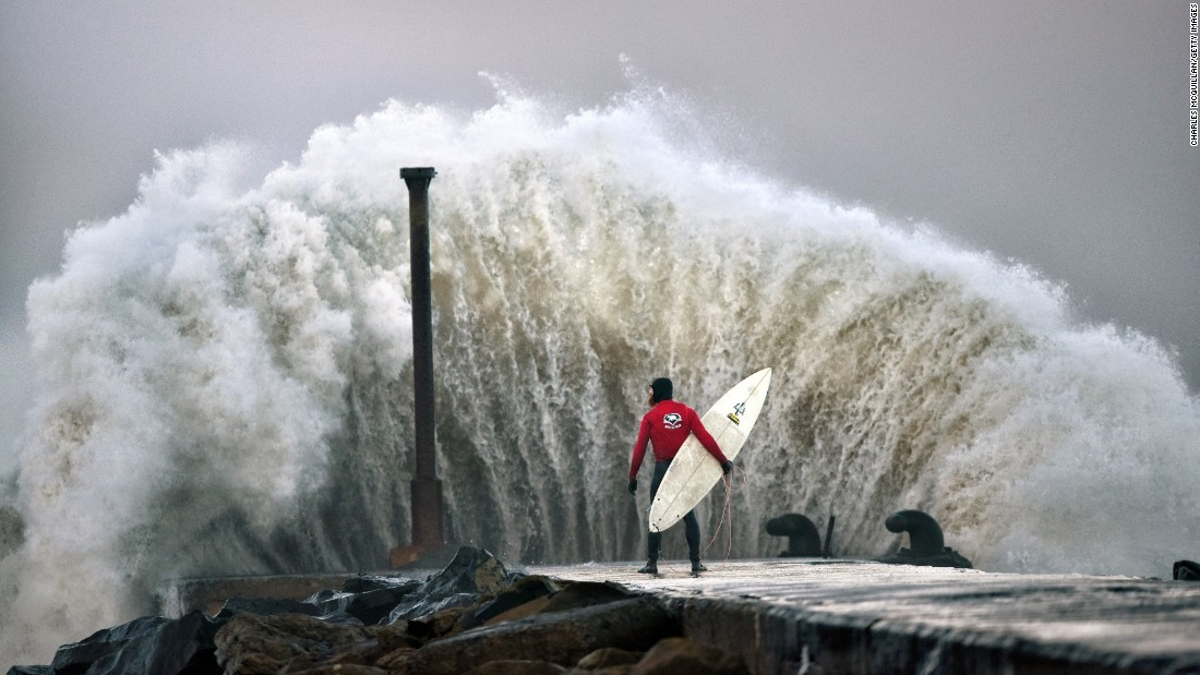 Professional surfer Al Mennie watches as a huge wave crashes against Castlerock pier during Storm Barbara in Coleraine, Northern Ireland, on Thursday.