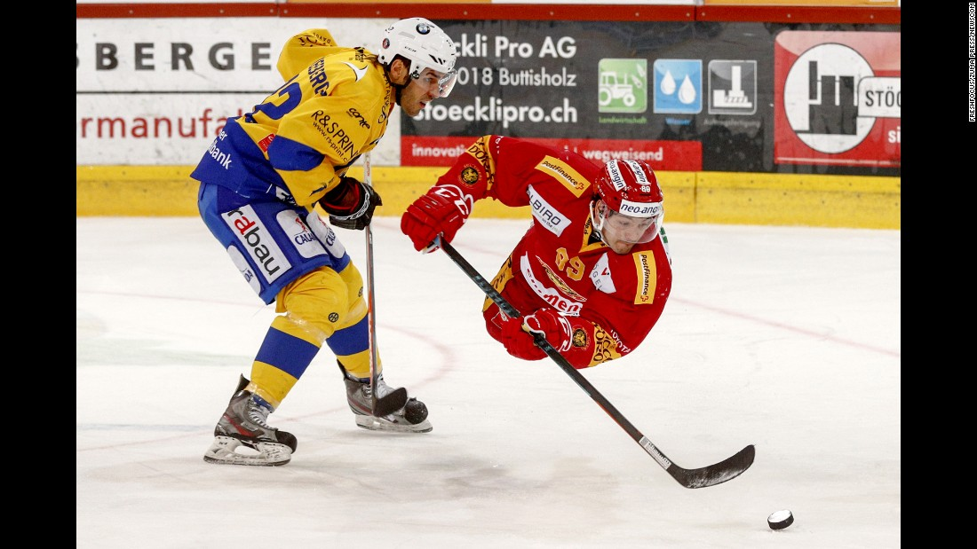 Davos' Noah Schneeberger, left, and Evgeni Chiriaïev of Langnau go for the puck during a Swiss league ice hockey game in Langnau, Switzerland, on Friday.