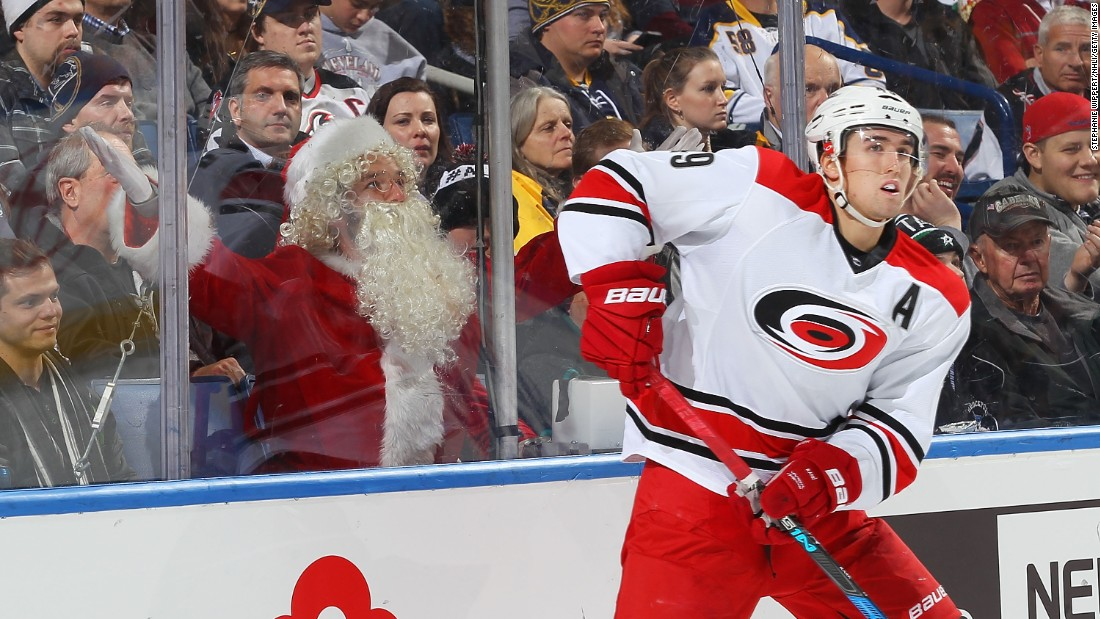 An ice hockey fan dressed as Santa Claus reacts as Carolina's Victor Rask controls the puck against Buffalo during an NHL game in Buffalo, New York, on Thursday. Carolina won 3-1.