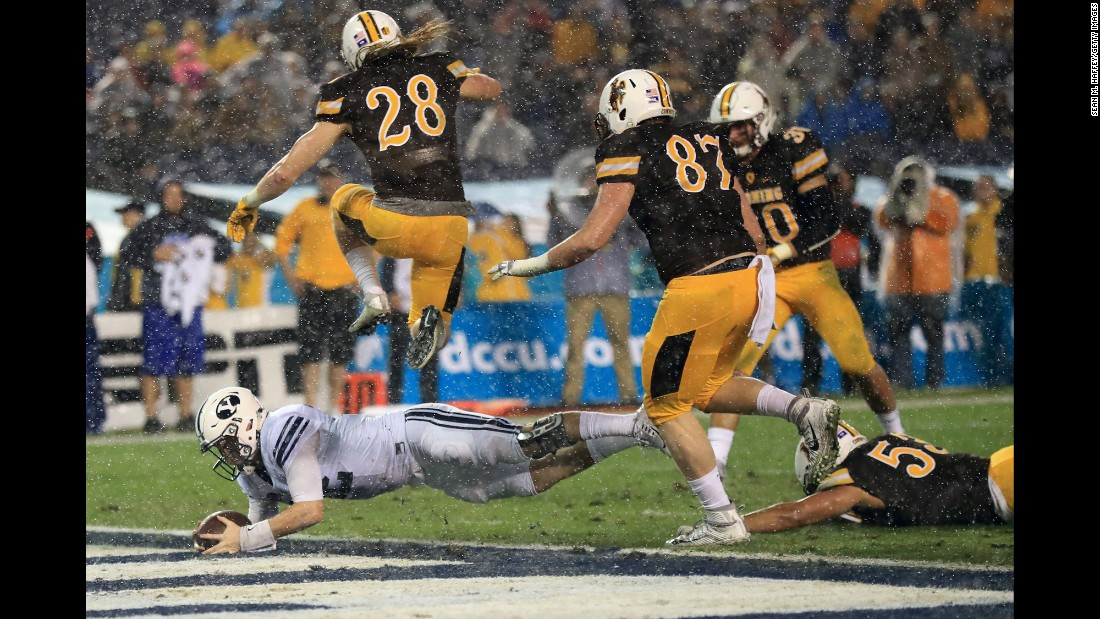 Brigham Young's Tanner Mangum dives for a touchdown against Wyoming during a Poinsettia Bowl college football game in San Diego on Wednesday. Wyoming lost 21-24.