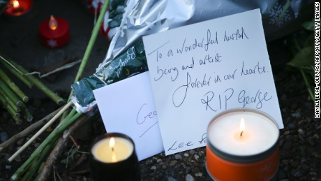 Messages and candles are seen among floral tributes outside the singer's home.