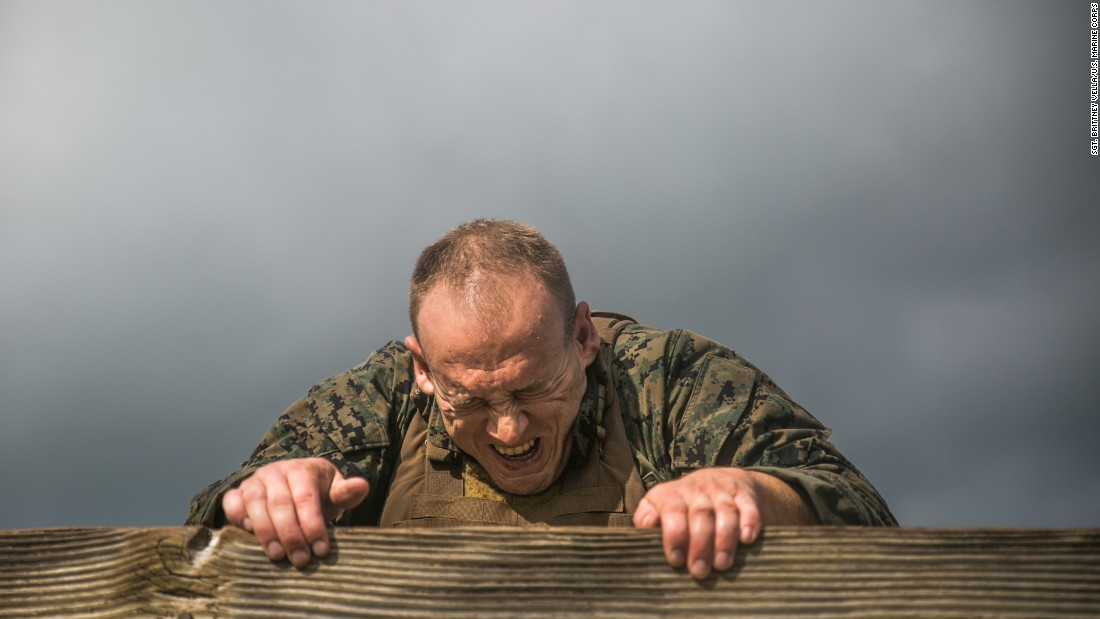 Staff Sgt. Ryan Molina scales a wall while completing an obstacle course at the Marine Corps Base Hawaii naval station on Thursday, December 15. Molina was taking part in a Martial Arts Instructor Course (MAIC), a rigorous three-week exercise designed to instill teamwork and develop leadership abilities.