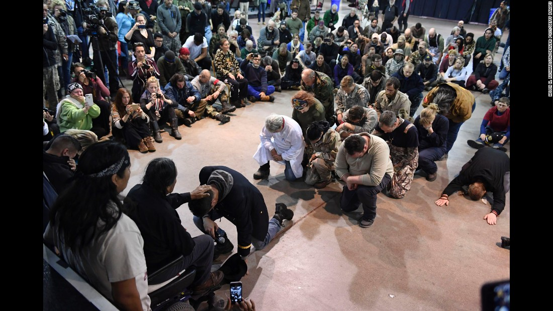 Wesley Clark Jr. kneels in front of Leonard Crow Dog during a forgiveness ceremony at the Standing Rock Sioux Reservation in Fort Yates, North Dakota, on Monday, December 5. A group of US veterans asked Native Americans to forgive the military actions carried out against Native American people throughout history.