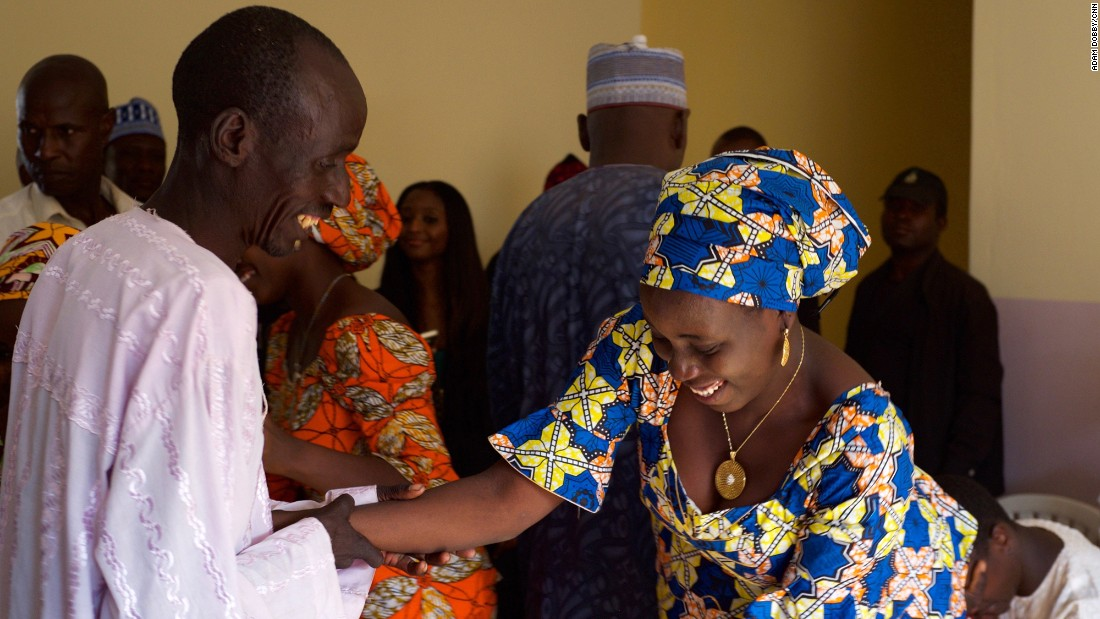A father greets his daughter after she arrived with 20 other freed Chibok girls.<br />