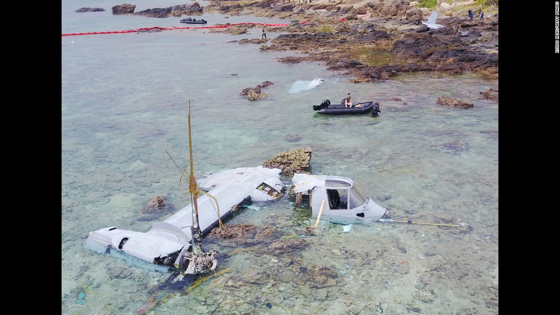 US military personnel recover the wreckage of an MV-22 Osprey aircraft on the coast of Nago, Japan, on Thursday, December 15, after it crash-landed two days earlier.
