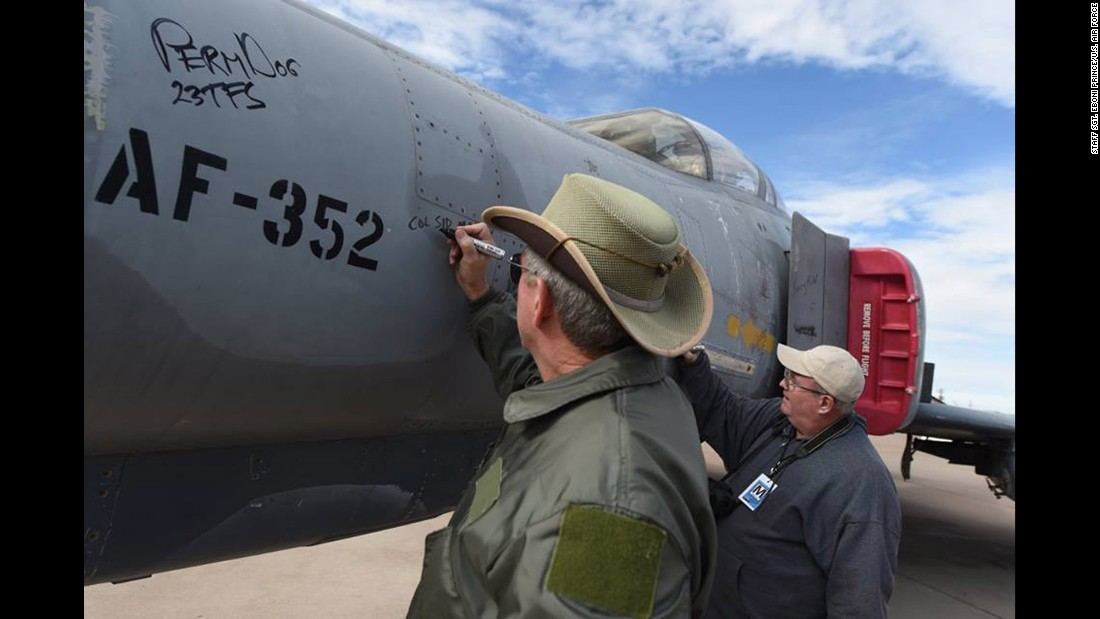 "A veteran pens his signature on a QF-4 Phantom during a ""Pet the Jet"" portion of the Phinal Phlight commemoration at Holloman Air Force Base in New Mexico on Wednesday, December 21. To date, the QF-4 Phantom has flown approximately 145 unmanned sorties."