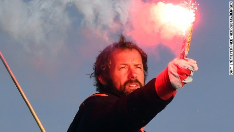 "French skipper Thomas Coville holds a burning flare onboard his ""Sodebo Ultim'"" multihull as he arrives in the port of Brest, western France, on December 26, 2016, after beating the record in solo non-stop round the world sailing. Coville, 48, slashed eight days off the record when he ended an astonishing solo non-stop circumnavigation of the World on his 31m maxi trimaran on December 25, 2016, in just 49 days, 3 hours, 7mins and 38secs.  / AFP / Damien MEYER        (Photo credit should read DAMIEN MEYER/AFP/Getty Images)"