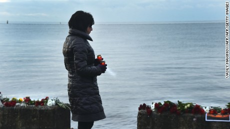 A woman holds candles at a memorial on a pier outside Sochi, on December 26, 2016, as Russia observes a national day of mourning a day after a military plane carrying 92 people, including dozens of members of the Red Army Choir, crashed in the Black Sea. The Russian defence ministry told agencies there was no sign of any survivors at the crash site and that 10 bodies had been recovered off the coast of the resort city of Sochi, as authorities pledged to dispatch an additional 100 divers to aid in the search.  / AFP / VASILY MAXIMOV        (Photo credit should read VASILY MAXIMOV/AFP/Getty Images)
