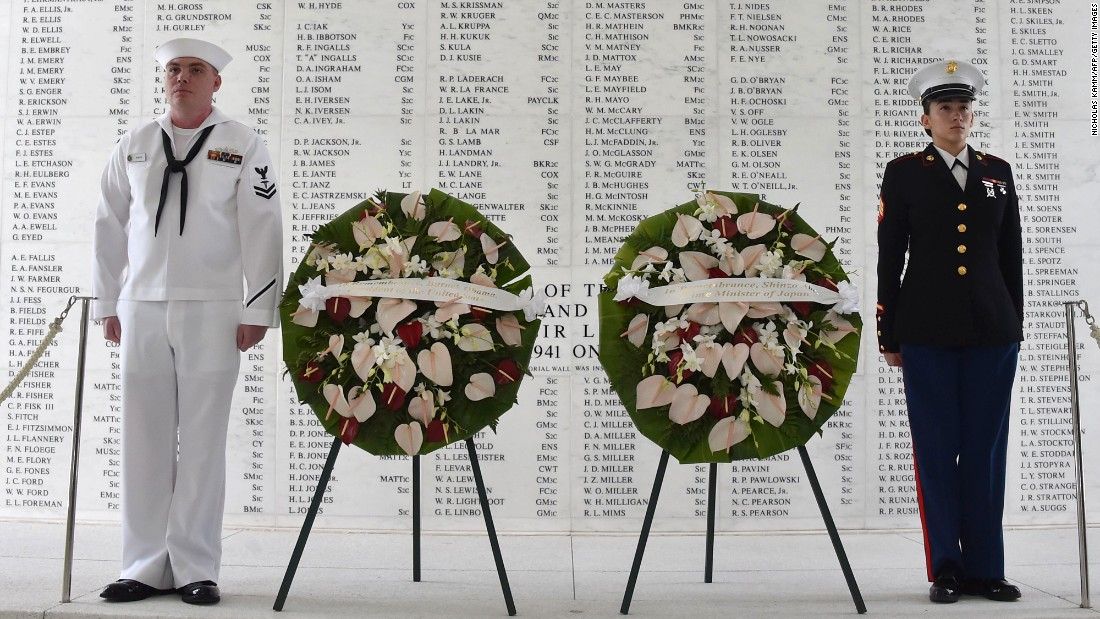 Two members of the US military stand at attention after Obama and  Abe laid wreaths at the USS Arizona Memorial.