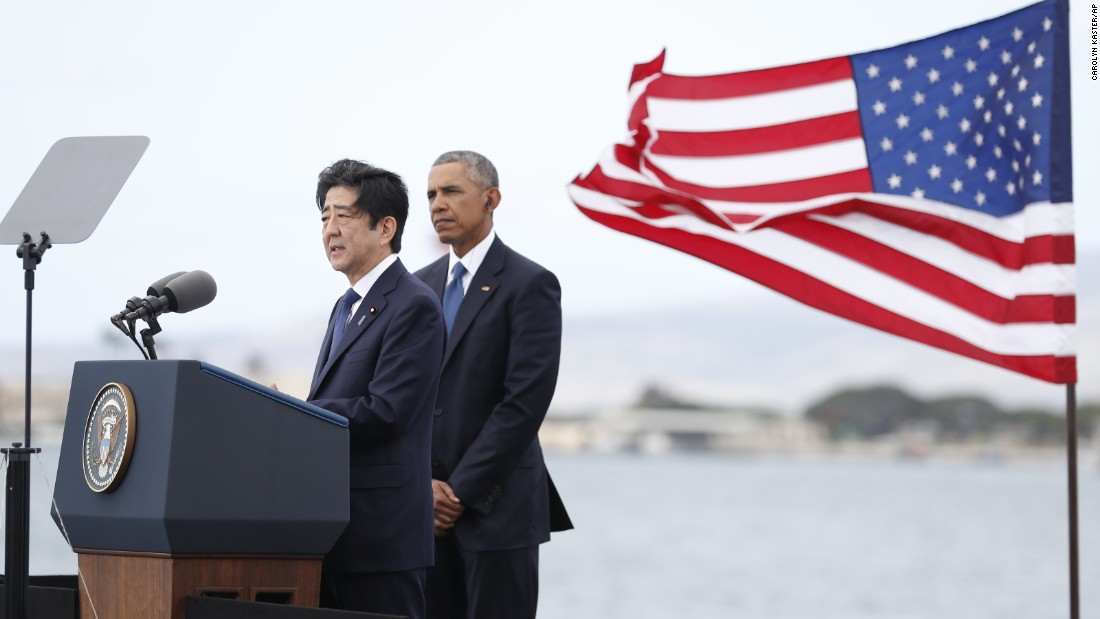 President Barack Obama listens as Japanese Prime Minister Shinzo Abe speaks on Kilo Pier overlooking the USS Arizona Memorial in Joint Base Pearl Harbor-Hickam, Hawaii, on Tuesday, December 27. His remarks were part of a ceremony to honor those killed in the Japanese attack on the naval harbor. Abe is the first Japanese prime minister to visit Pearl Harbor with a US president and the first to visit the USS Arizona Memorial.