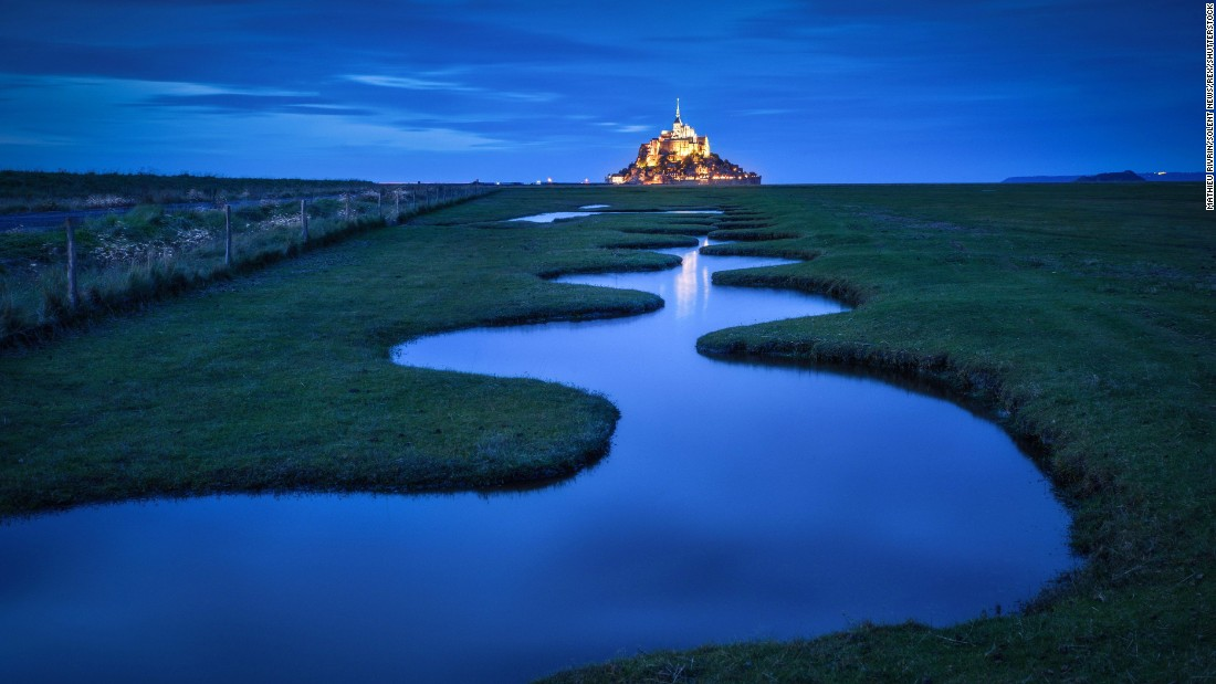 The abbey at Mont Saint Michel, an island community in Normandy, France, is a UNESCO World Heritage Site. About 40 to 50 people live in the medieval walled city, which hosts more than a million tourists each year. High tide turns the abbey into an island.