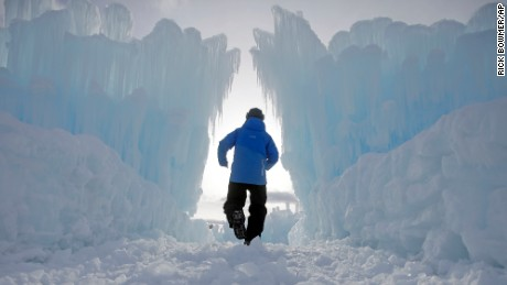 A worker walks through the Ice Castles during final preparations Tuesday, Dec. 27, 2016, in Midway, Utah. Hundreds of thousands of icicles make up the 20-foot walls, jagged mazes and fountains of the castle. The public will be able to walk through the maze of ice starting Tuesday night. Visitors are able to interact with the castle as there is a slide, mazes, canyons, tunnels and fountains. (AP Photo/Rick Bowmer)