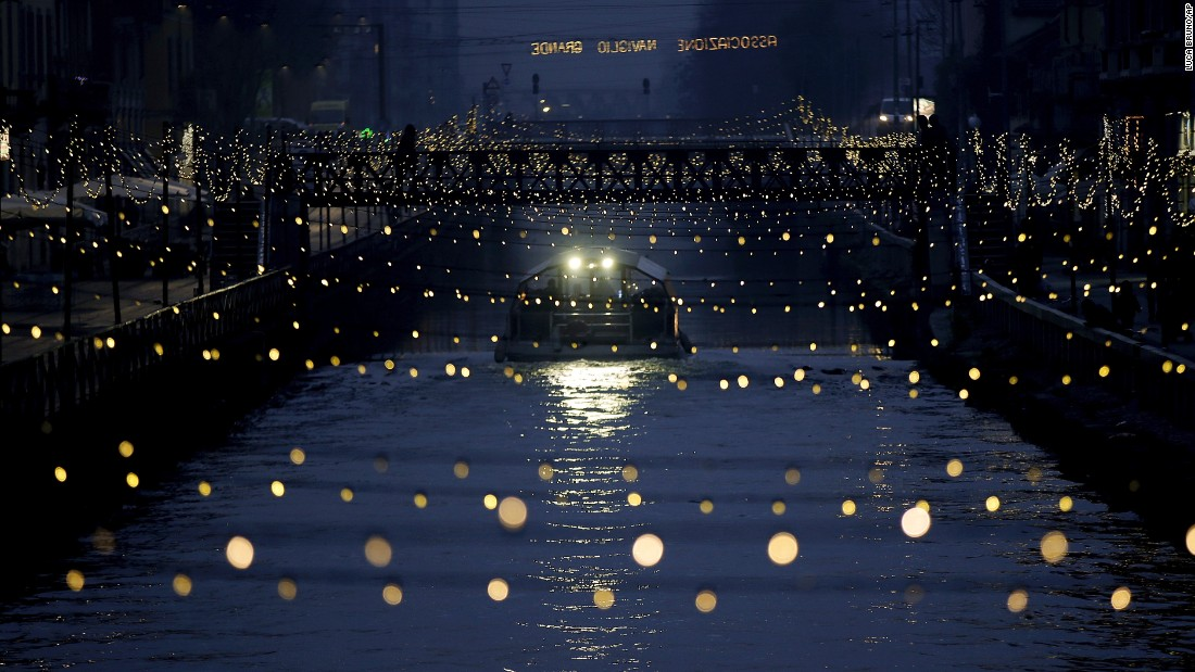 A tourist boat sails beneath Christmas lights illuminating Darsena dei Navigli, a Milan neighborhood named for the canals that run through it.