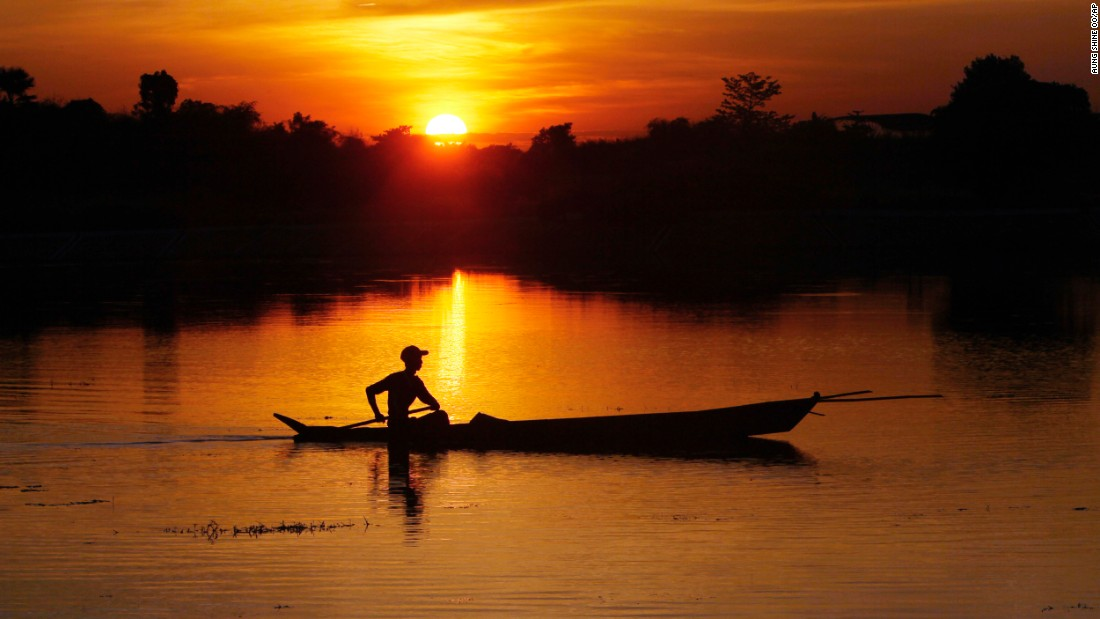 As the sun sets in Naypyitaw, Myanmar, a fisherman paddles his boat on a lake.