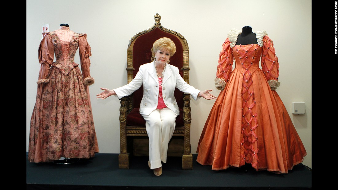 "Reynolds poses before the auction of her massive collection of memorabilia from classic movies in 2011. Reynolds is siting on the throne from the 1955 movie ""Virgin Queen"" with a dress worn by Bette Davis, right,  and Joan Collins, left."