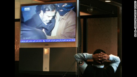An Iraqi policeman watches a broadcast of Saddam Hussein moments before his execution.