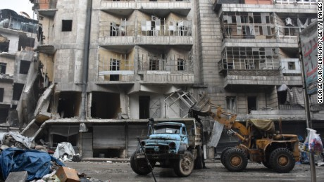A tractor removes rubble as the Syrian government starts to clean up areas formerly held by opposition forces in the northern city of Aleppo on December 27, 2016, in the Shaar district.