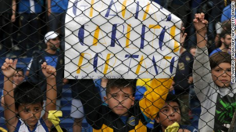 A boy holds placard with legends of gratitude to forward Carlos Tevez --referring to his impending transfer of  to the Chinese football-- during their Argentina First Division football match against Colon at La Bombonera stadium, in Buenos Aires, on December 18, 2016. / AFP / ALEJANDRO PAGNI        (Photo credit should read ALEJANDRO PAGNI/AFP/Getty Images)