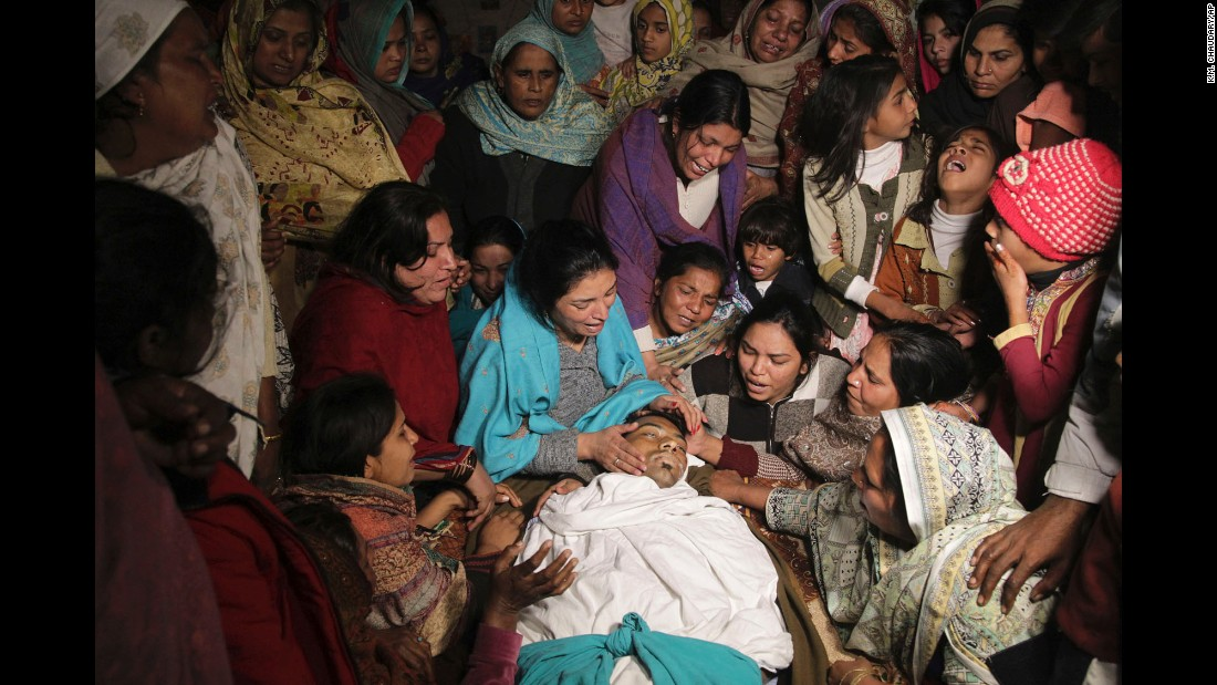<strong>December 28:</strong> Women mourn the death of a family member in Toba Tek Singh, Pakistan. Local police said dozens of people were killed and many transported to hospitals after they consumed contaminated alcohol during the Christmas holidays.
