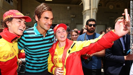 Federer poses for selfies with surf lifesavers at Cottesloe Beach.