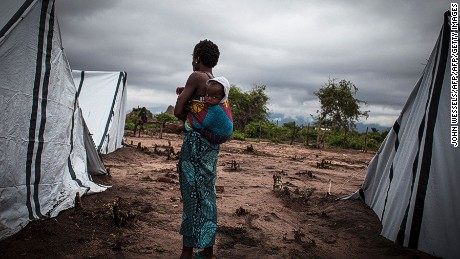TOPSHOT - An internally displaced Mozambican woman holds her baby on her back as she stands by two tents in an internal displacement camp on December 12, 2016 in Vanduzi in the Manica Province. This year has seen a sharp escalation in violence, and more than 15,000 people have been forced to flee to government-run camps, relatives' homes or across the border to Malawi and Zimbabwe. The clashes between longtime rivals, the Frelimo government and Renamo, an armed insurgent group and also an elected opposition party, have revived the spectre of Mozambique's civil war that ended more than 20 years ago. / AFP / John WESSELS        (Photo credit should read JOHN WESSELS/AFP/Getty Images)