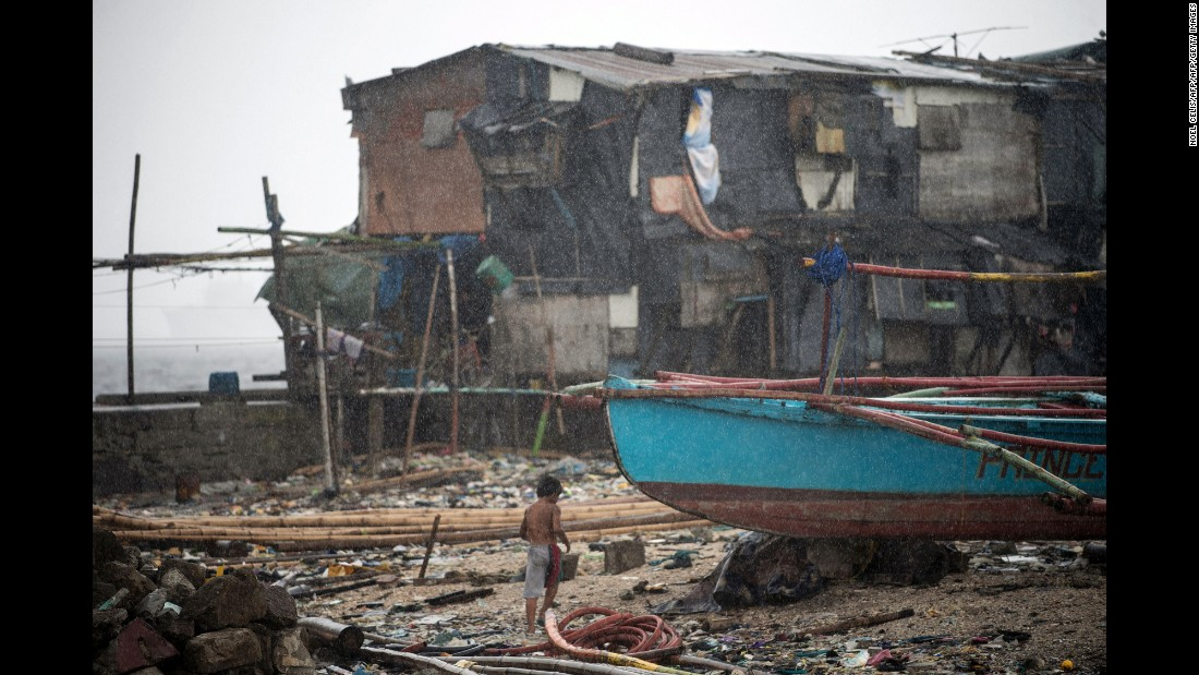 "A boy runs for cover in the rain after <a href=""http://www.cnn.com/2016/12/25/asia/typhoon-nock-ten-nina-philippines/"" target=""_blank"">Typhoon Nock-Ten</a> makes landfall in  Manila, Philippines, on Monday, December 26."