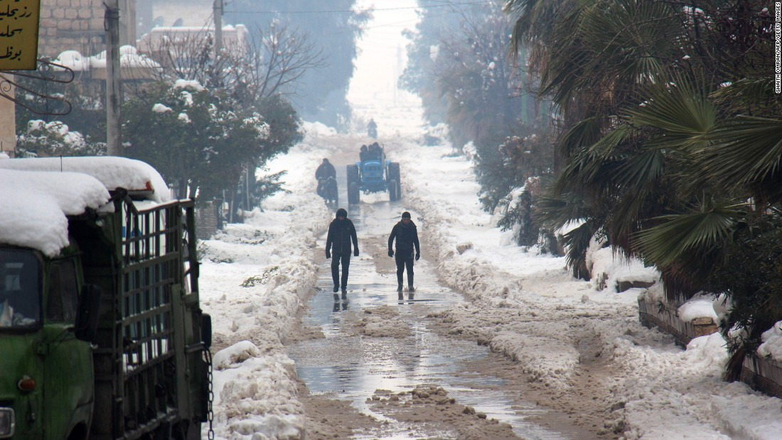 Syrians walk in a snow-covered street in the town of Maarat al-Numan, in Syria's northern province of Idlib, on Thursday, December 22.