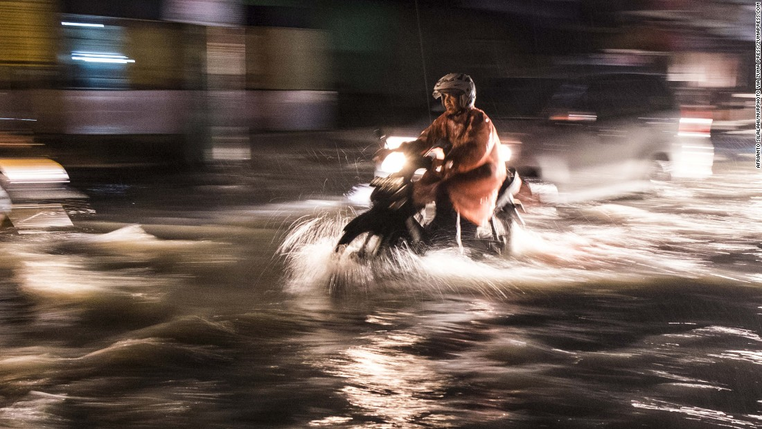 Vehicles pass through a flooded road in Pekanbaru, Indonesia, following heavy rains, on December 22.