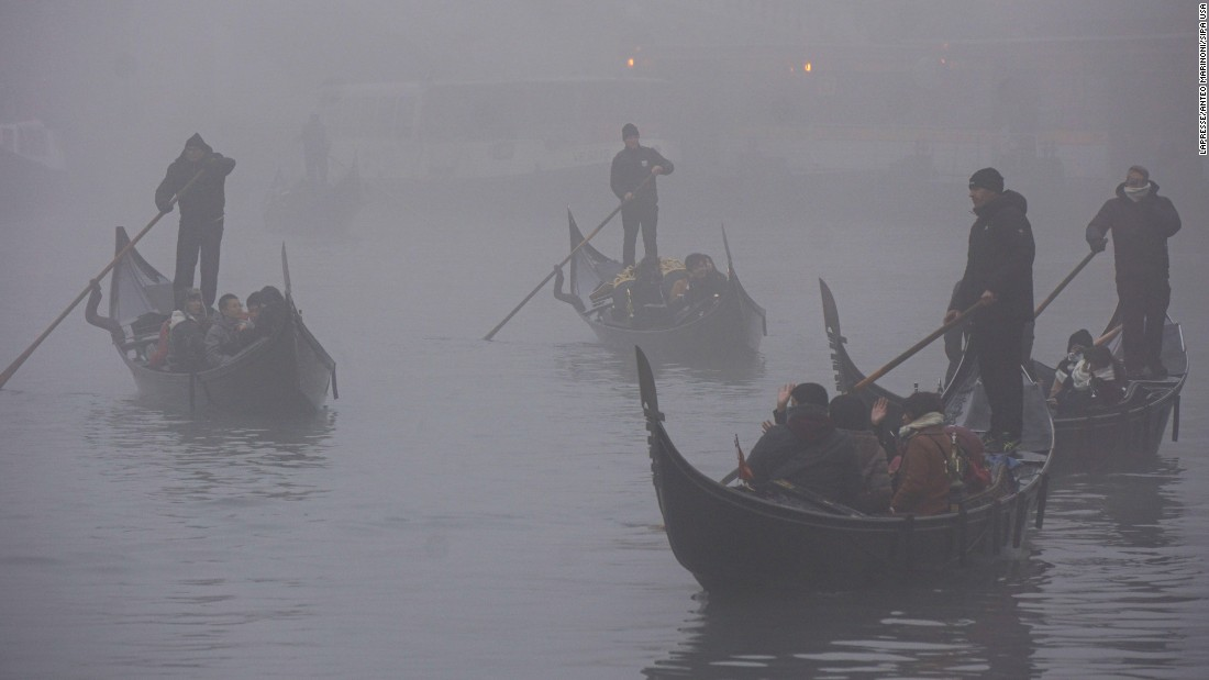 Gondolas drift through the fog in Venice, Italy, on Saturday, December 10.