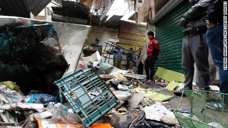 Iraqis look at the aftermath following a double blast in a busy market area in Baghdad's central al Sinag street on December 31, 2016.