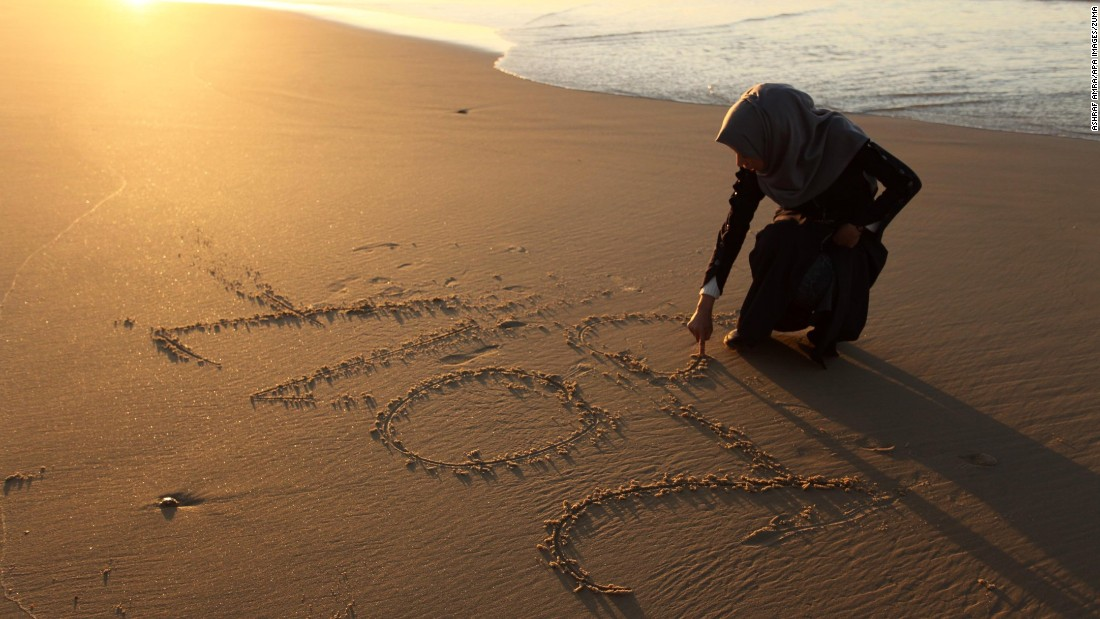 "A Palestinian girl writes ""2017"" on the sand during the last sunset of 2016 on a beach in Gaza City on New Year's Eve."