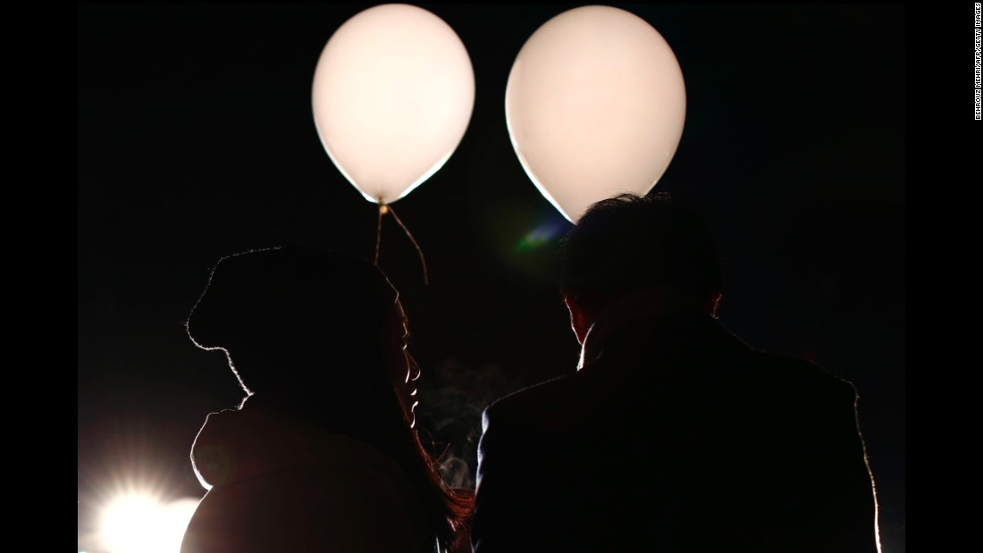 A couple holds balloons containing their wishes for the new year during celebrations at Prince Park Tower in Tokyo, Japan.