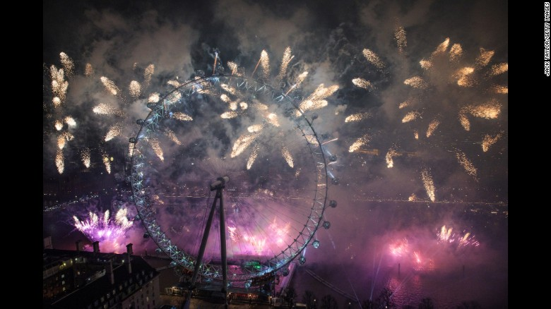Fireworks are lit near the London Eye just after midnight in London, England.