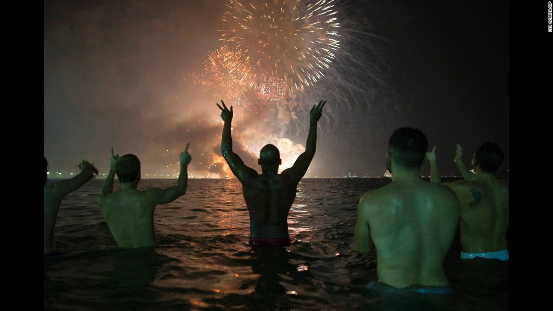 People watch fireworks explode over Copacabana Beach during celebrations in Rio de Janeiro, Brazil.