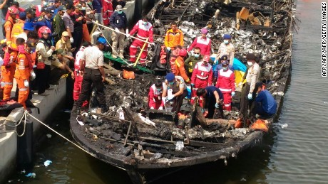 Rescuers search the charred passenger boat which was ferrying around 200 people off the coast of Jakarta to Tidung island, a tourist destination close to the capital when a fire started on January 1, 2017.