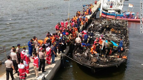 Rescuers search the charred passenger boat.